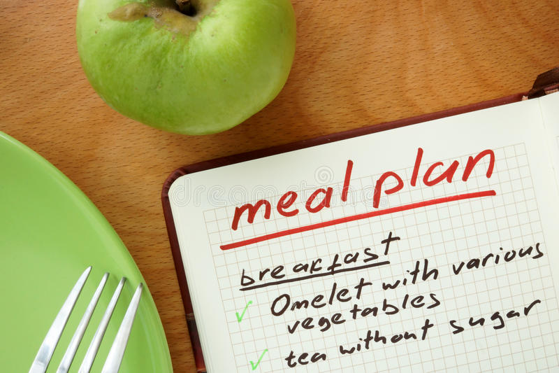 Notepad with words meal plan and apple. Weight lose concept stock image