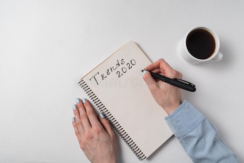 Notepad with words Trends 2020. Female hands and cup of coffee on white background. Top view stock photo