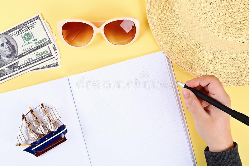 notepad yellow background, sun glasses, hat, money. Top view.copy space. Summer background, travel stock photography