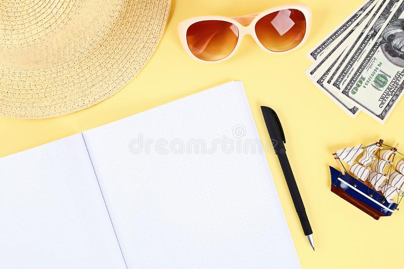 Notepad yellow background, sun glasses, hat, money. Top view.copy space. Summer background, travel. Blank notepad on a yellow background, sun glasses, hat, money royalty free stock photography