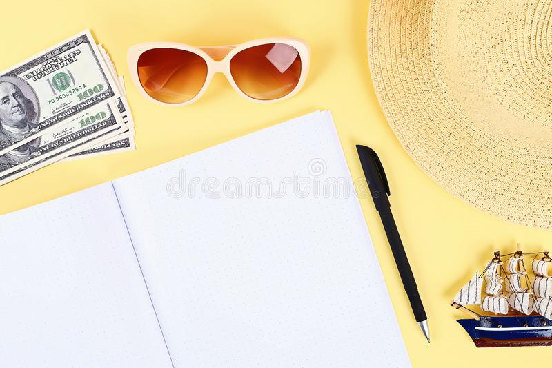 Notepad yellow background, sun glasses, hat, money. Top view.copy space. Summer background, travel. Blank notepad on a yellow background, sun glasses, hat, money royalty free stock images