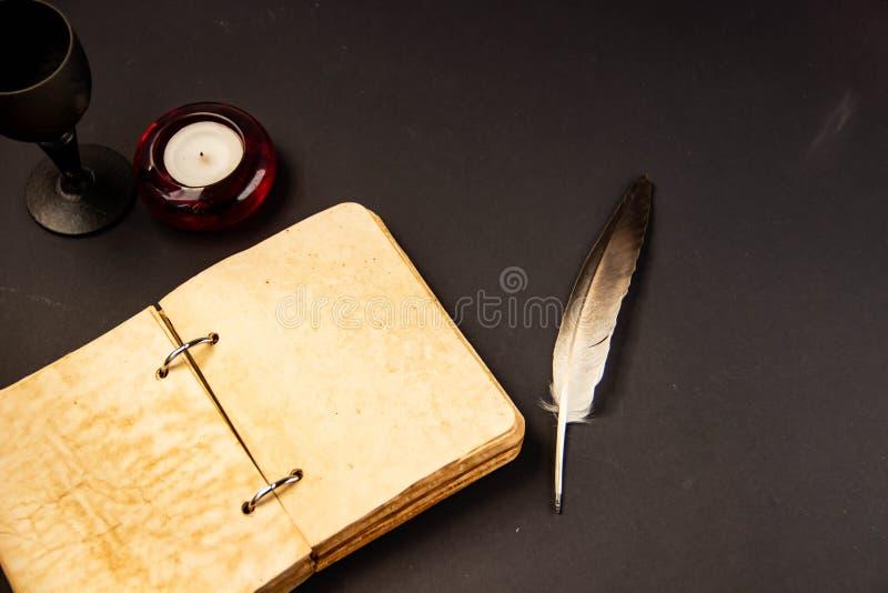 Notepad z piórem od pióra i czerwieni świeczka na czarnym tle zdjęcie royalty free