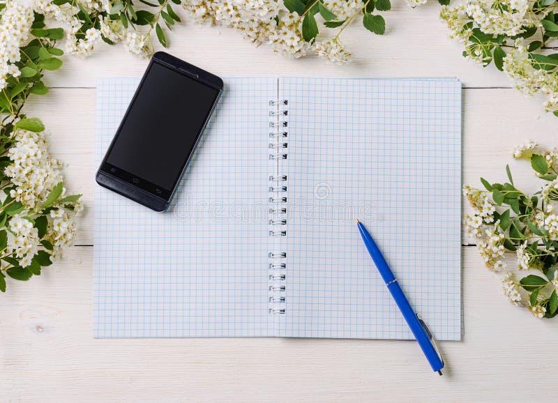 Notepaden, mobiltelefonen och pennan med den lösa våren blommar arkivbilder