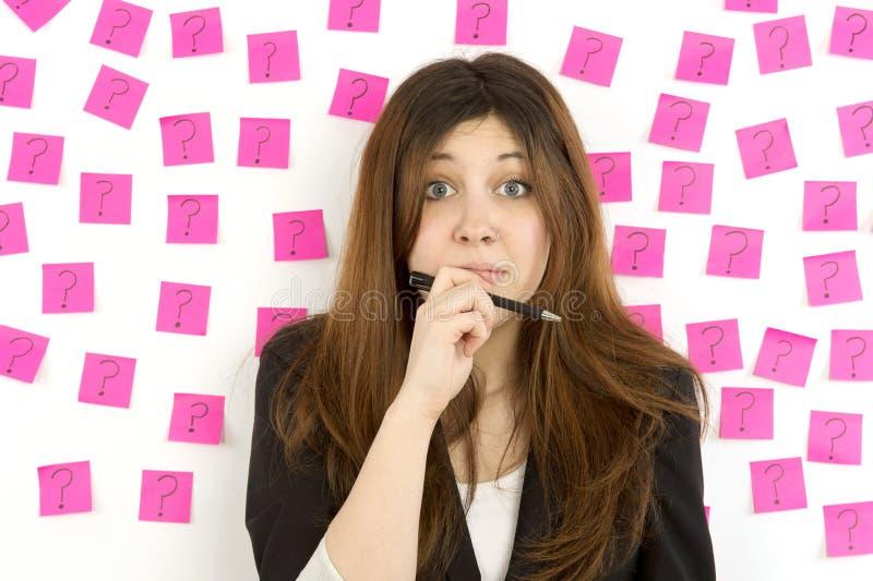 Noterar rosa klibbigt för ung kvinna ifrågasätter markerar arkivbild
