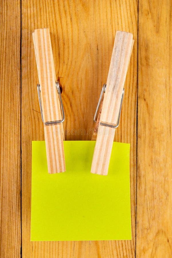 Notes collantes colorées accrochées sur les agrafes en bois Notes collantes pour des rappels économisants sur une table en bois photos libres de droits
