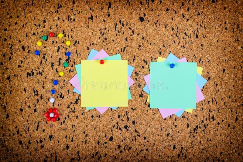 Notes collantes colorées sur des babillards de liège Point d'interrogation fait de punaises photos stock