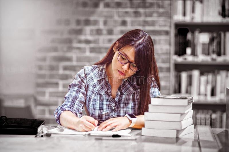 Notes d'écriture d'étudiante dans la bibliothèque images stock