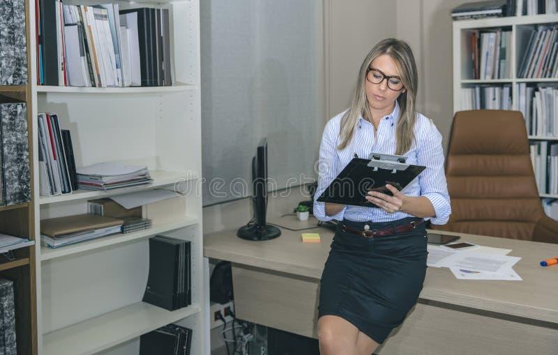 Notes d'écriture de jeune femme sur son lieu de travail images stock