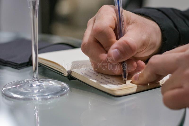 Notes d'écriture d'homme pendant un échantillon de vin image stock