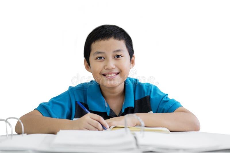 Notes de la préadolescence asiatiques d'écriture de garçon dans le studio photos stock