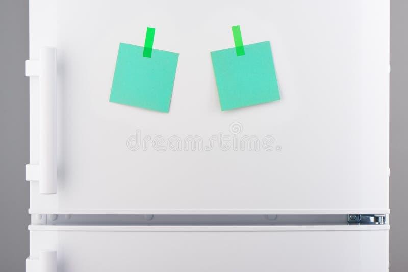 Notes de Livre vert jointes en annexe avec des autocollants sur le réfrigérateur blanc photo stock