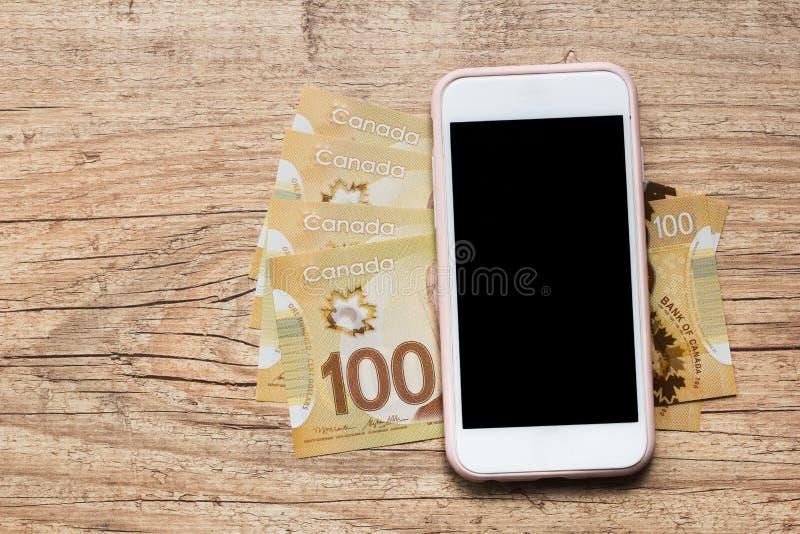 Notes de papier de Canada Dollar Factures vides d'écran et d'argent liquide de smartphone sur la table en bois photographie stock libre de droits