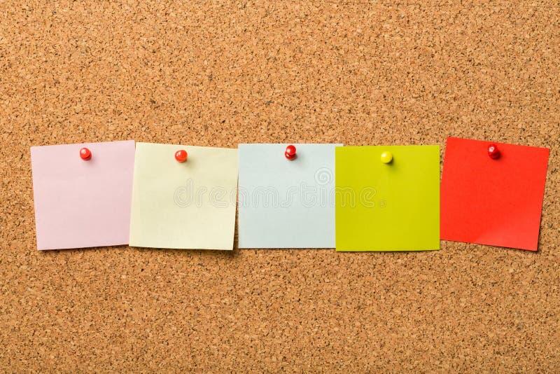Notes de papier goupillées sur le panneau de liège image libre de droits