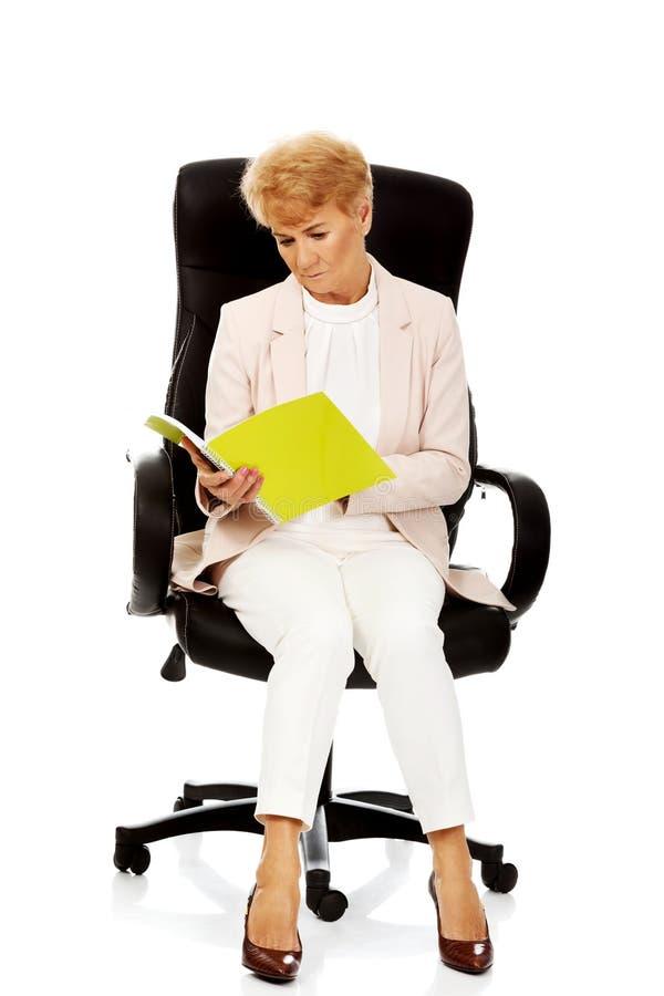 Notes focalisées songeuses pluses âgé de lecture de femme d'affaires photo libre de droits