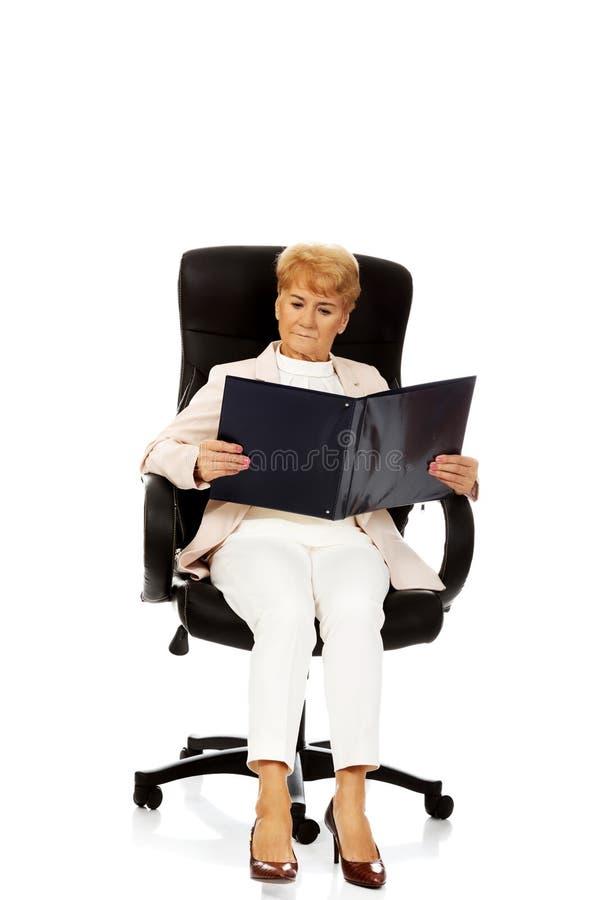 Notes focalisées songeuses pluses âgé de lecture de femme d'affaires photos stock