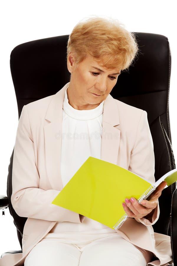 Notes focalisées songeuses pluses âgé de lecture de femme d'affaires photo stock