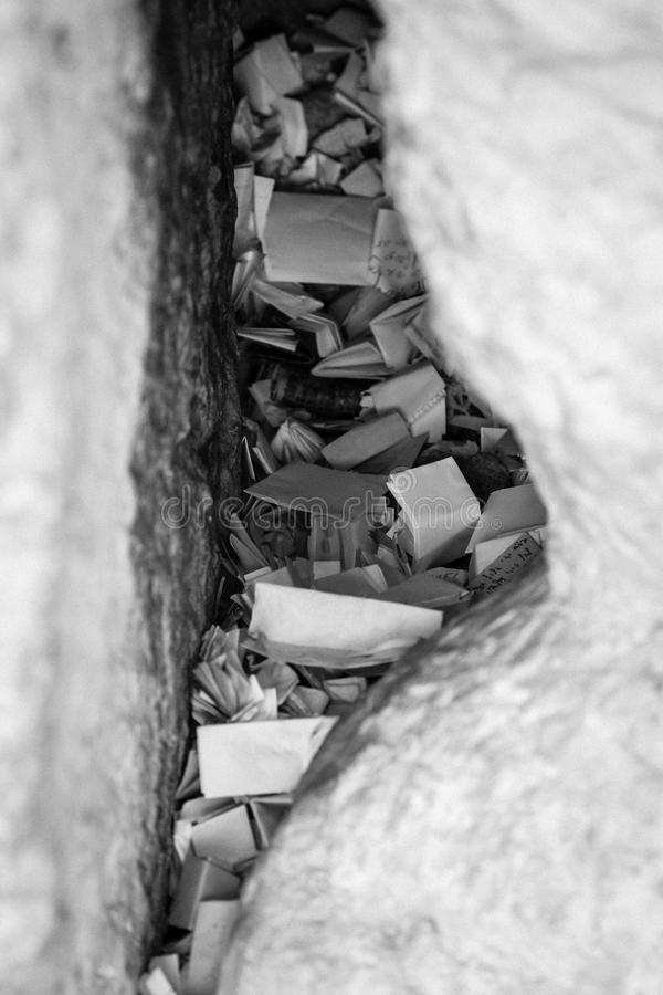 Notes in a gap of the wailing wall in black and white royalty free stock photography