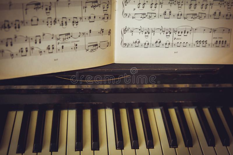 The notes lie on a black piano. White keys stock photo