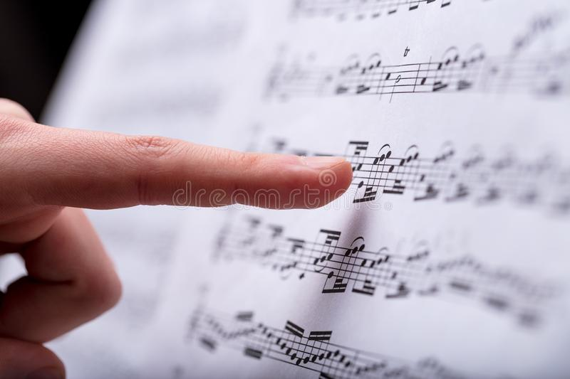 Notes on a musical score spotted by finger. Musical score with some notes in it pointed out by a woman`s finger spotting some detail stock images