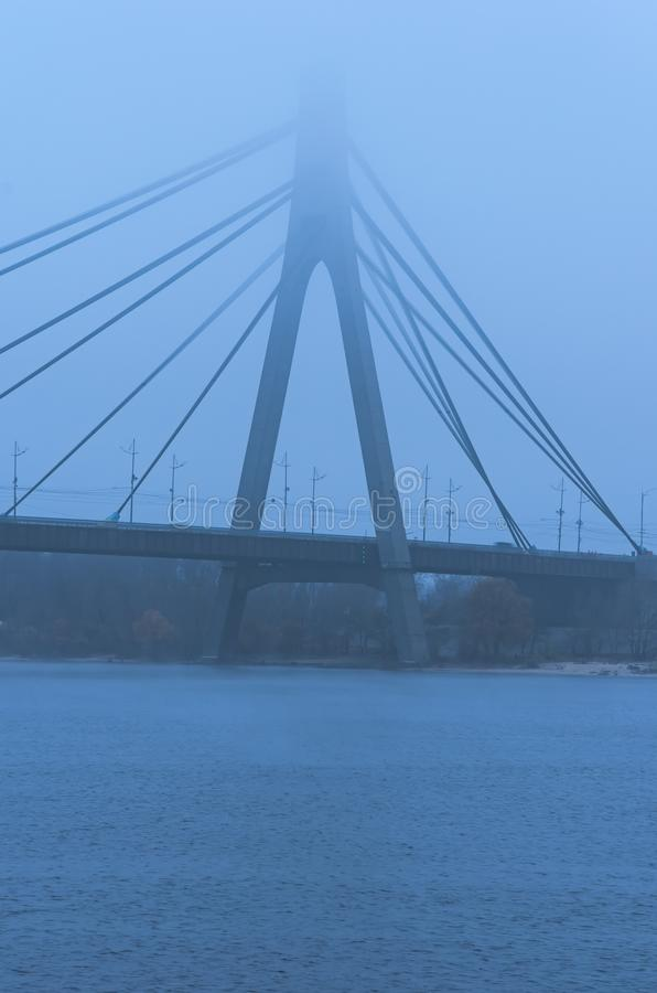 Nothern Moscow Bridge in thick fog. Misty landscape. Bad autumn weather. The concept of foggy weather in the city. Kyiv, Ukraine royalty free stock photo