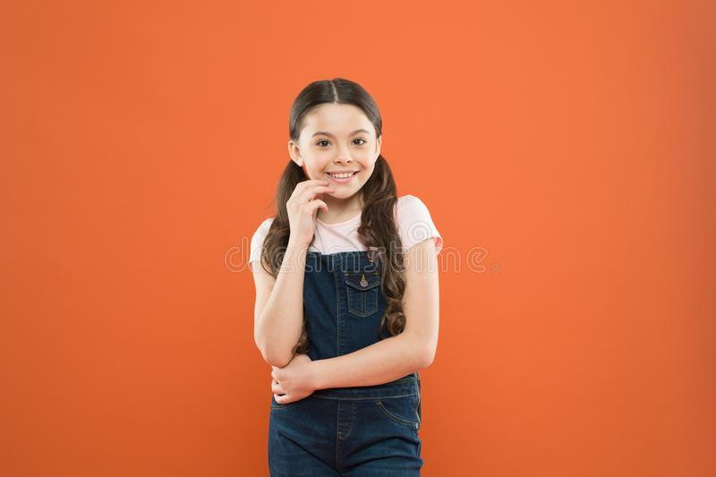 Nothing beats a great smile. Adorable little girl with big smile on orange background. Smiling child with white healthy. Smile on beautiful face. Cute small kid stock photography