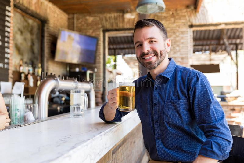 Nothing Beats The Refreshment Of Cold Beer. Happy man enjoying cold beer on counter at restaurant stock photo