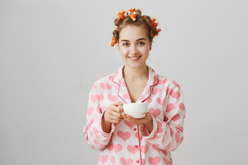 Nothing can be better than coffee in morning. Portrait of attractive friendly woman at home wearing hair curlers and royalty free stock images