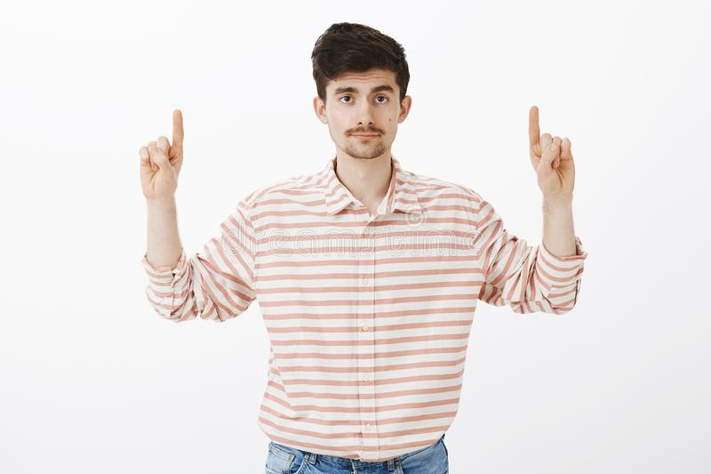Nothing interesting here. Portrait of indifferent unimpressed handsome guy with beard and moustache, raising hands stock image