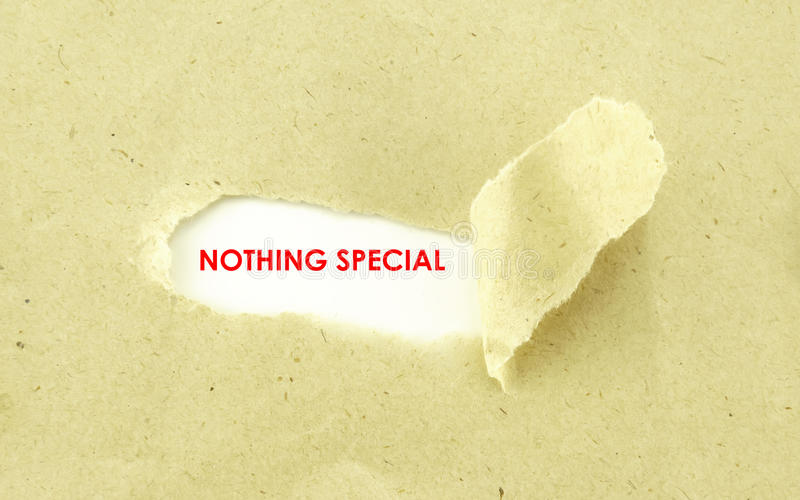 NOTHING SPECIAL. Text NOTHING SPECIAL appearing behind torn light brown envelope royalty free stock image