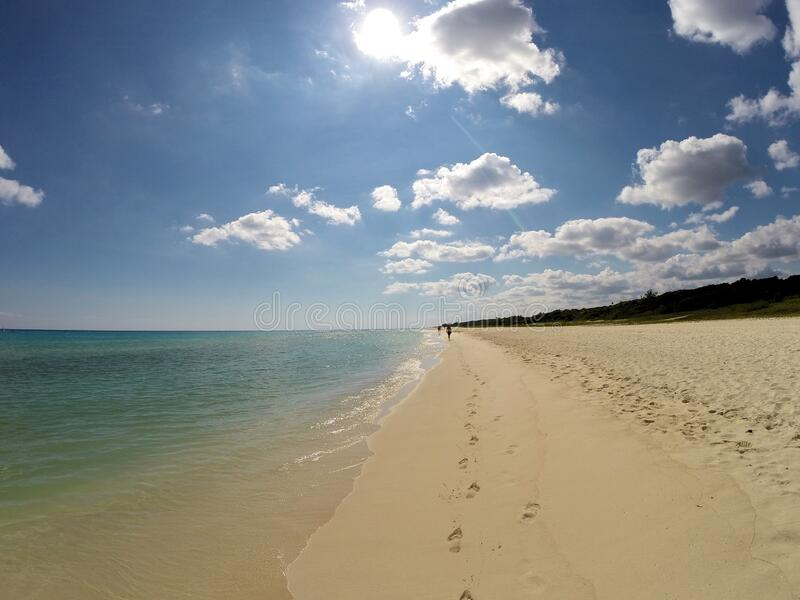 Footprints in the Sand. Nothing but sun, sand, footprints, water and blue sky on this deserted section of beach in Playa del Carmen stock image