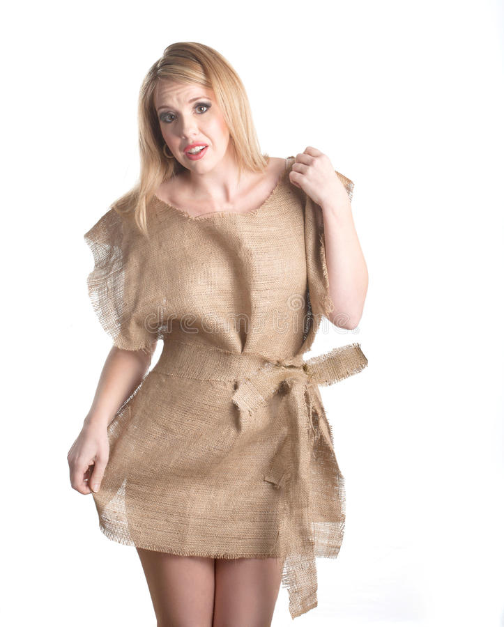 Nothing to wear. An attractive young woman shows her frustration as she wears a rough burlap dress. She is indicating she has nothing to wear stock photography