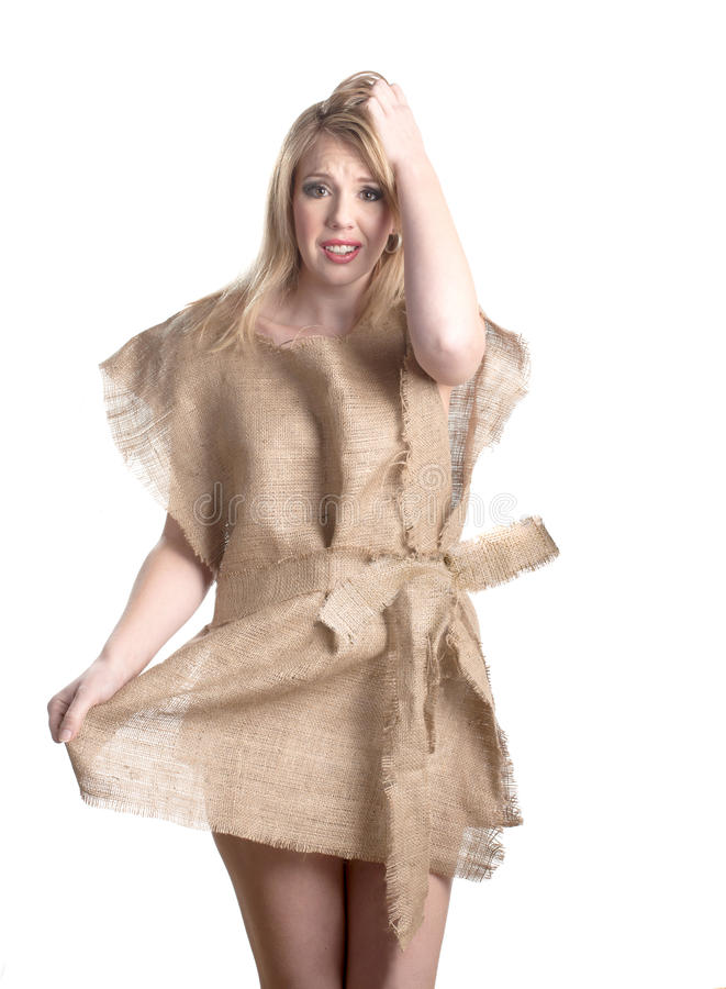 Nothing to wear. An attractive young woman shows her frustration as she wears a rough burlap dress. She is indicating she has nothing to wear royalty free stock photos