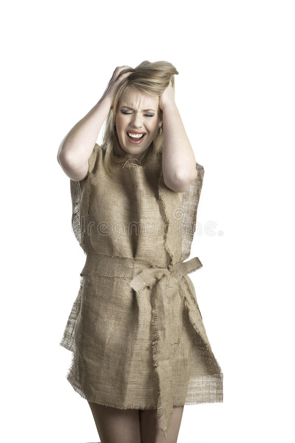 Nothing to wear. An attractive young woman shows her frustration as she wears a rough burlap dress. She is indicating she has nothing to wear stock images