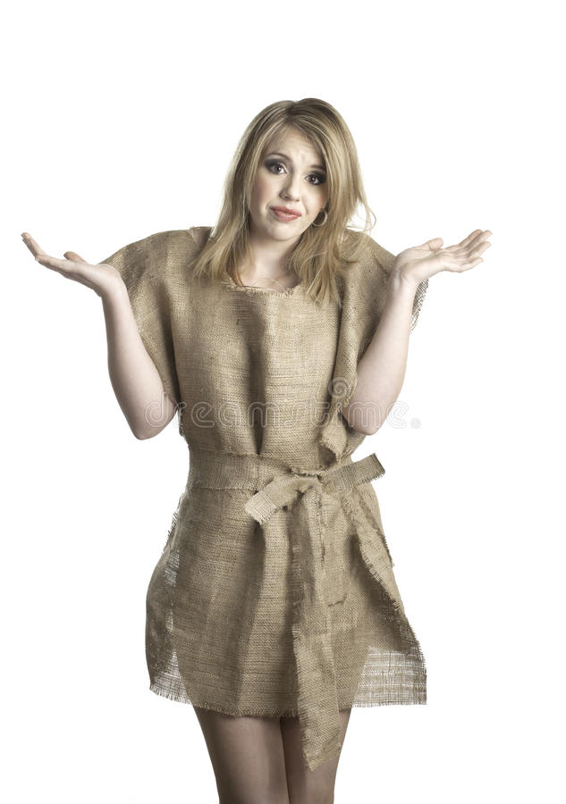 Nothing to wear. An attractive young woman shows her frustration as she wears a rough burlap dress. She is indicating she has nothing to wear royalty free stock image