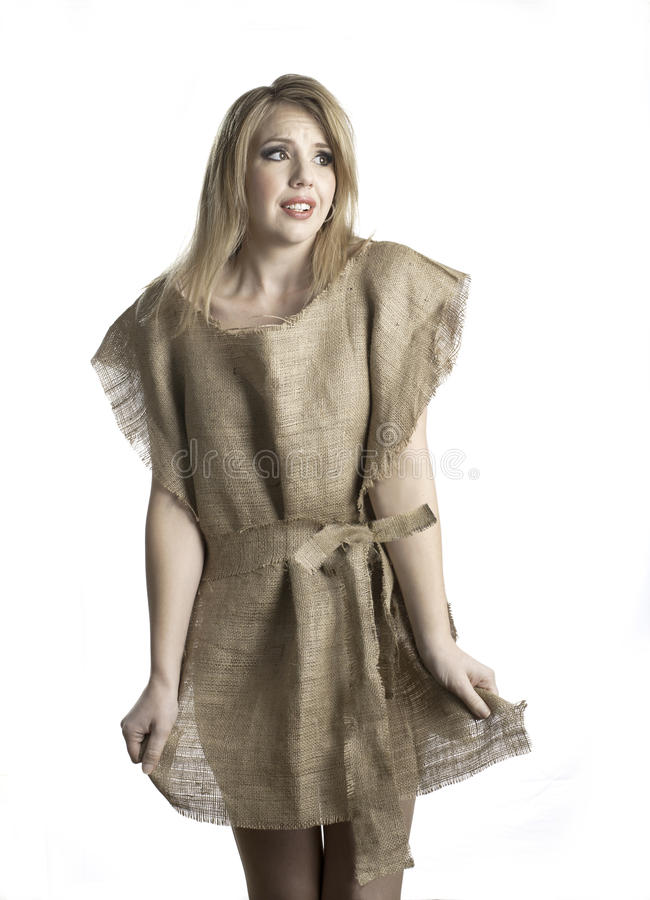 Nothing to wear. An attractive young woman shows her frustration as she wears a rough burlap dress. She is indicating she has nothing to wear stock photo