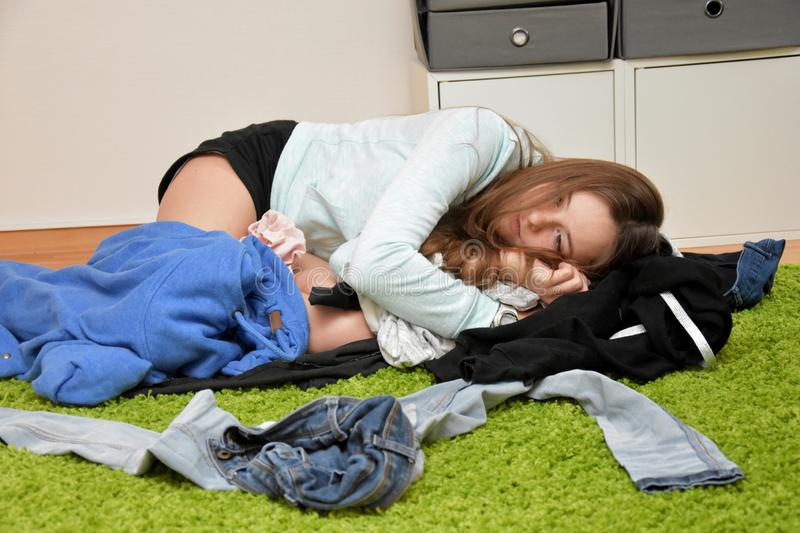 Dissatisfied teenage girl lying on the floor in the chaos  of  her outfit. Nothing to wear. Teenage girl lying  on the floor churns frustrated her clothes stock image