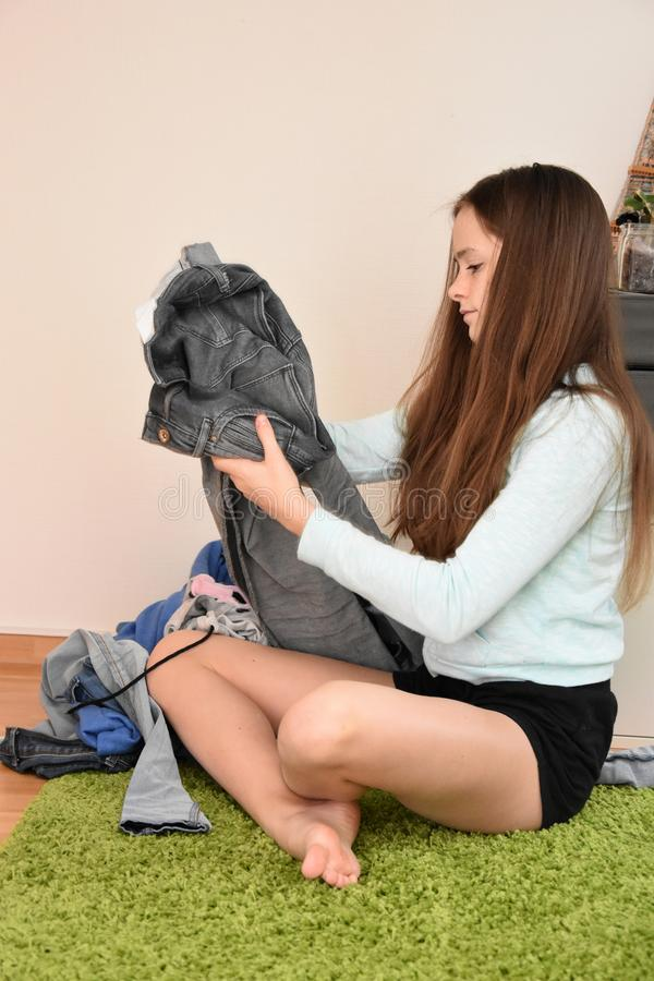 Dissatisfied teenage girl choosing her outfit. Nothing to wear. Teenage girl sits on the floor looking frustrated at her clothes stock images