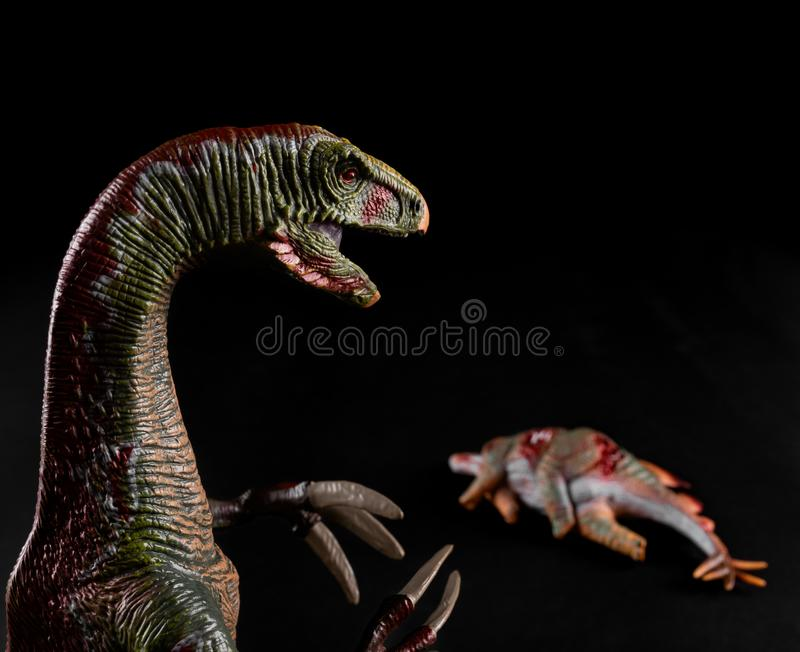 Nothronychus na frente do corpo do stegosaurus no fundo escuro fotografia de stock