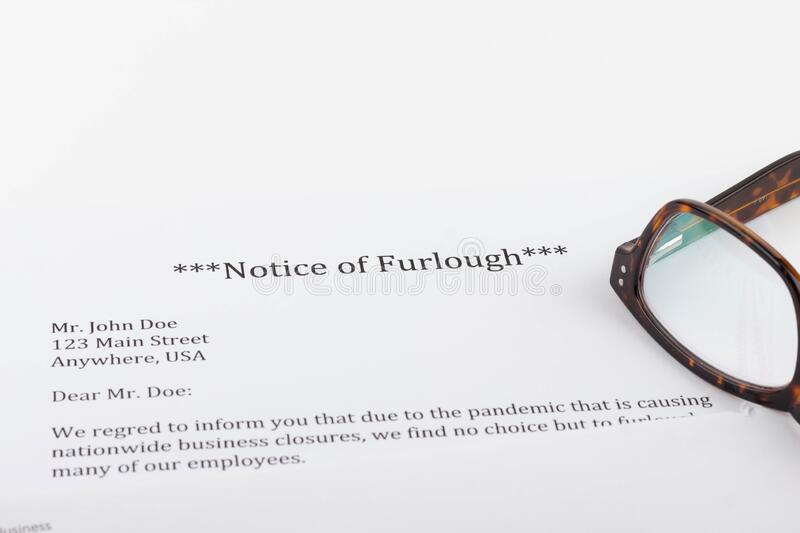 A notice of furlough lays on a table with an envelope, computer, notebook, and reading glasses. During the  COVID-19 pandemic, people will likely be furloughed royalty free stock photo