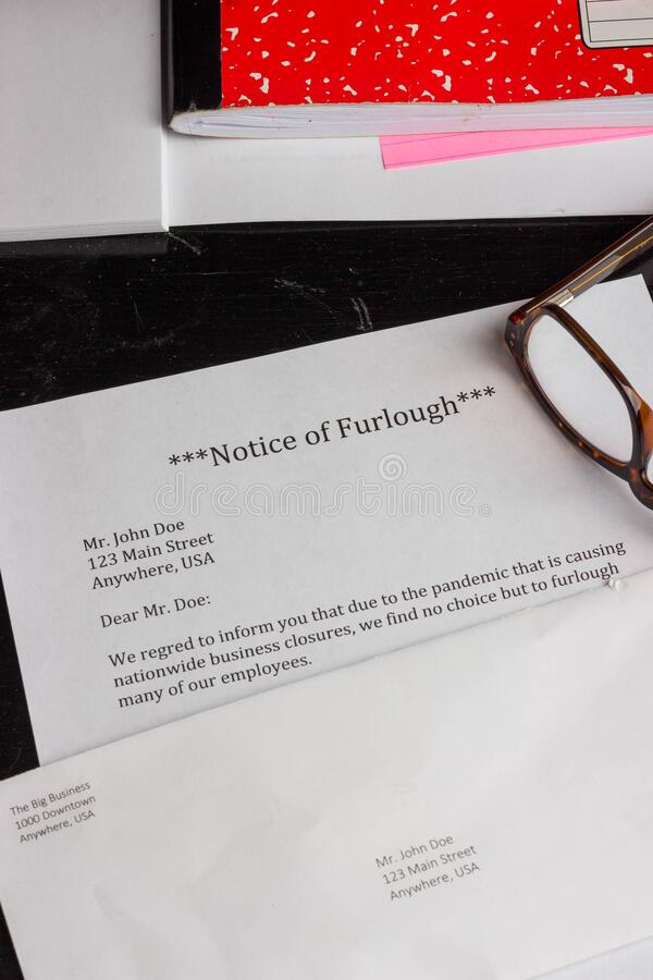 A notice of furlough lays on a table with an envelope, computer, notebook, and reading glasses. During the  COVID-19 pandemic, people will likely be furloughed royalty free stock images