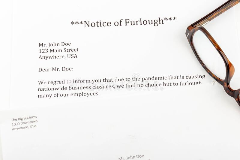 A notice of furlough lays on a table with an envelope, computer, notebook, and reading glasses. During the  COVID-19 pandemic, people will likely be furloughed stock image