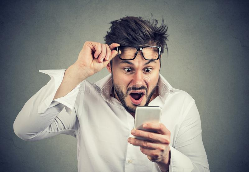 Noticias chocadas de la lectura del hombre en smartphone imagenes de archivo