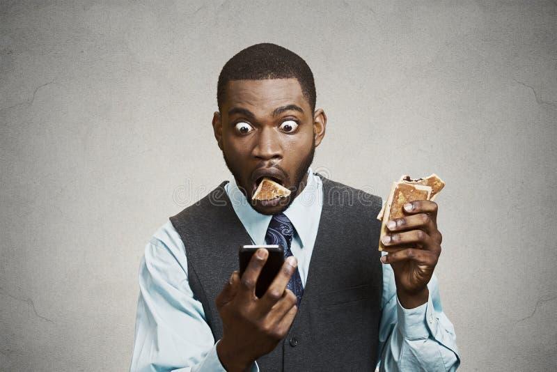 Noticias de última hora chocadas de la lectura del hombre de negocios en el teléfono mientras que come fotografía de archivo libre de regalías