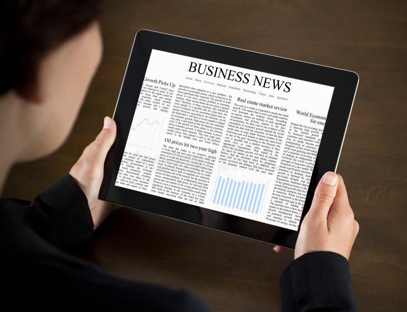 Noticias de asunto de la lectura en la PC de la tablilla foto de archivo
