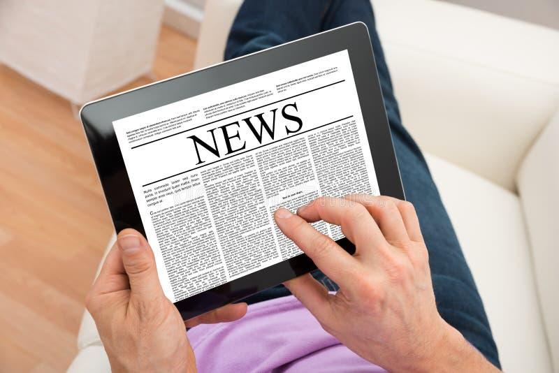 Noticias de la lectura del hombre en la tableta digital fotos de archivo