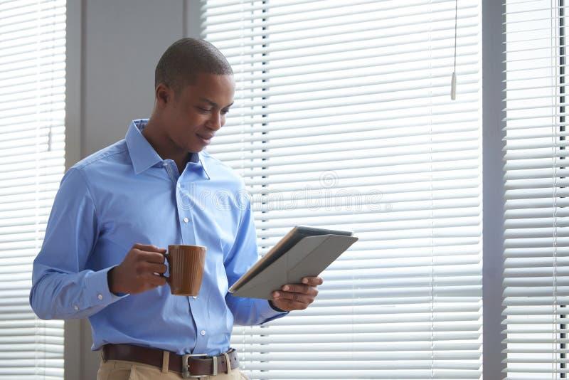Noticias de la lectura del hombre de negocios en línea foto de archivo