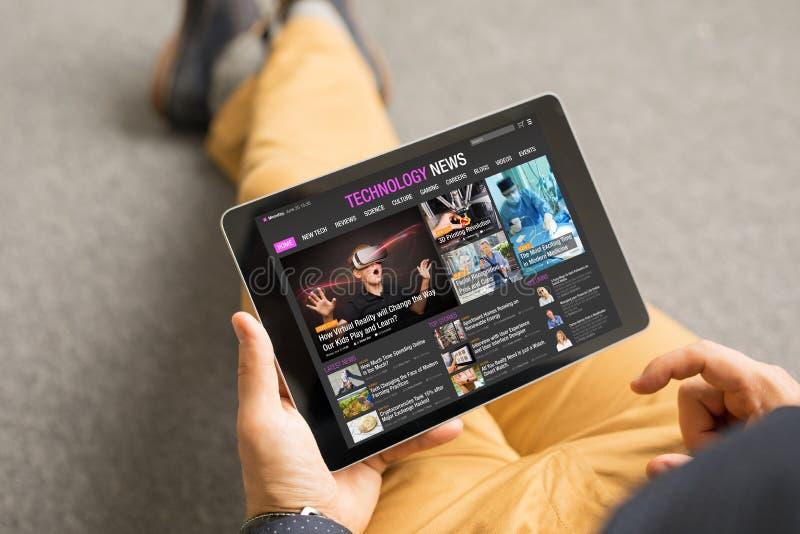 Noticias de la tecnología de la lectura del hombre en la tableta foto de archivo libre de regalías