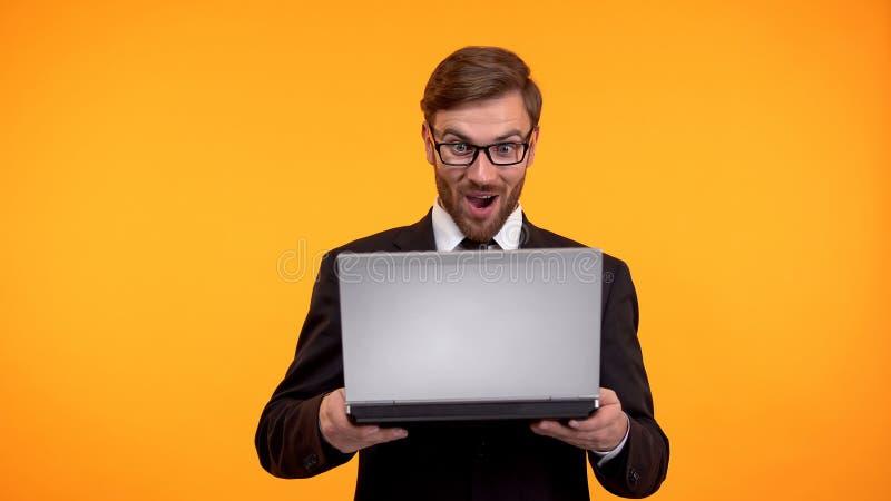Noticias de lectura sorprendidas en el ordenador port?til, compras en l?nea, venta del hombre buenas de la tienda de Internet imagenes de archivo