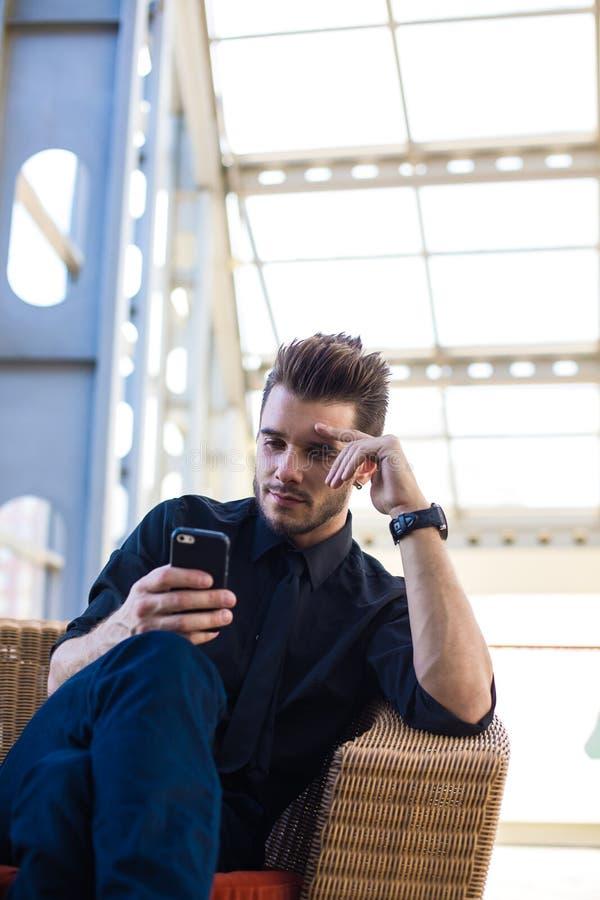 Noticias de negocio orgullosas de la lectura del CEO del hombre en Internet vía el teléfono de célula, sentándose en salida imagen de archivo libre de regalías