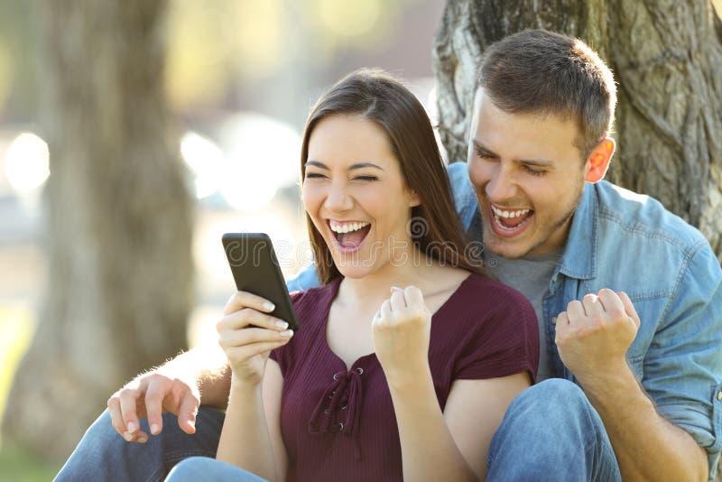 Noticias emocionadas de la lectura de los pares en un teléfono foto de archivo libre de regalías